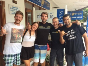 Another team of newly certified divers celebrate with a photo alongside their instructor